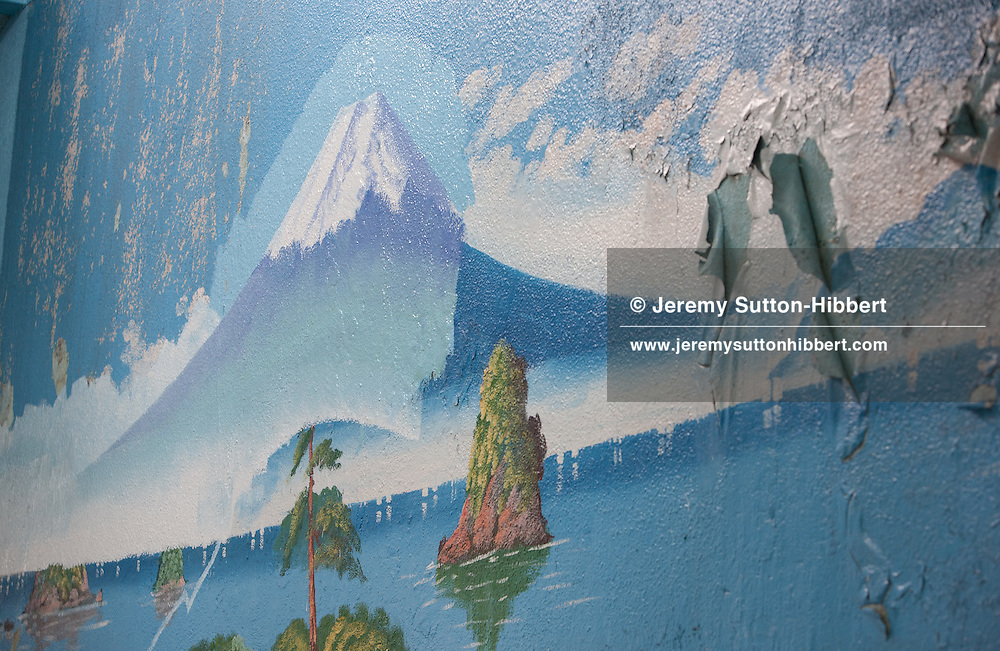 Penki-e (painter who uses paints) Morio Nakajima, and his apprentice of 6 years Mizuki Tanaka, paint a fresh mural of Mount Fuji over the top of an older similar view by painter Hayakawa Toshimitsu, at the 'Moto No Yu' sento (public bath house) in Shinozaki, in eastern Tokyo, Japan, on Thursday 23rd June 2011. Nakajima-san and Kiyoto Maruyama are the two remaining painters of Mt Fuji murals in the Kanto area of Japan. Nakajima-san currently undertakes approximately 70 such mural assignments a year, and they each cost the sento owners approximately JPY 100,000.  Mizuki Tanaka,  a graduate of art history, has been an apprentice to Nakajima-san for 6 years but has not yet progressed to the level where she is allowed to paint the Mt Fuji itself, at present she paints the other background details of the mural but not the mountain itself. Penki-e (painter who uses paints) Morio Nakajima (wearing yellow head towel), and his apprentice of 6 years Mizuki Tanaka (wearing green skip cap), paint a fresh mural of Mount Fuji over the top of an older similar view by painter Hayakawa Toshimitsu, at the 'Moto No Yu' sento (public bath house) in Shinozaki, in eastern Tokyo, Japan, on Thursday 23rd June 2011. Nakajima-san and Hayakawa-san are the two remaining painters of Mt Fuji murals in the Kanto area of Japan. Nakajima-san currently undertakes approximately 70 such mural assignments a year, and they each cost the sento owners approximately JPY 100,000.  Mizuki Tanaka,  a graduate of art history, has been an apprentice to Nakajima-san for 6 years but has not yet progressed to the level where she is allowed to paint the Mt Fuji itself, at present she paints the other background details of the mural but not the mountain itself.