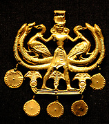 Sheet gold pendant showing a Cretan nature god, The figure wears a Minoan kilt, a tall head-dress, bracelets and earrings. He stands in the attitude of the 'Master of Animales'. In which a central figure flanked by animals demonstrates control over them. The curved, ridged elements surrounding the birds derive from stylised bulls' horns. Egyptian influence is seen in the lotus flowers among which he stands