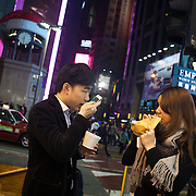 A young smart couple eat street food in Times Square at Christmas time.  7 million people live on 1,104km square, making it Hong Kong the most vertical city in the world.