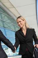 Businesswoman shaking hands with businessman outdoors