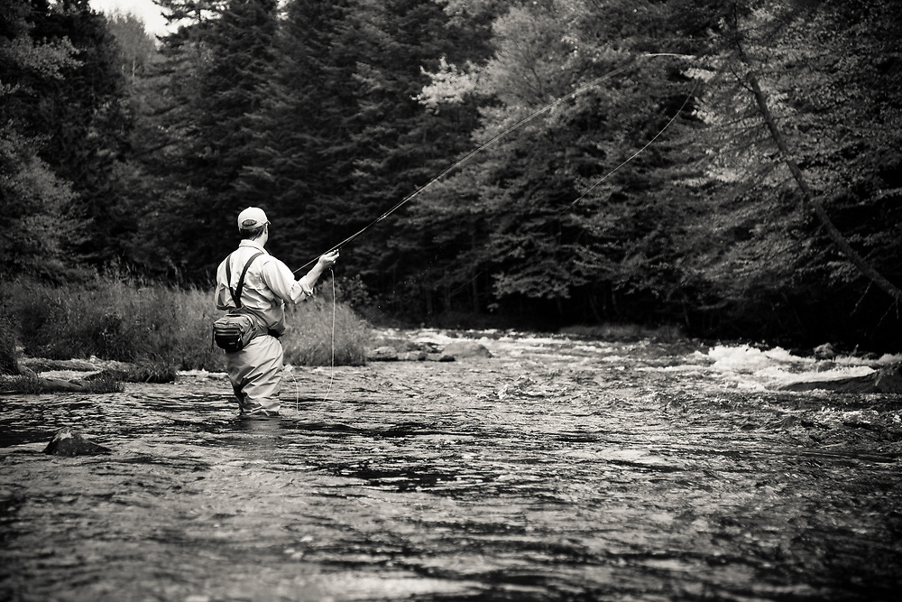 Male angler fly fishing for trout on the upper Connecticut River in northern New Hampshire.