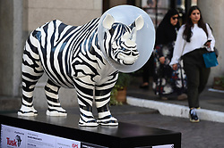 """**CAPTION CORRECTION - Rhino statues are 750mm tall, not 750cm tall, as stated in previous captions**<br /> © Licensed to London News Pictures. 20/08/2018. LONDON, UK. People pass by """"Going, Going, Gone"""", a rhino painted by Mauro Perucchetti, in Covent Garden.  At 750mm tall and weighing 300 kg, each rhino has been specially embellished by an internationally renowned artist.  21 rhinos are in place at a popular location in central London, forming the Tusk Rhino Trail, until World Rhino Day on 22 September to raise awareness of the severe threat of poaching to the species' survival.  They will then be auctioned by Christie's on 9 October to raise funds for the Tusk animal conservation charity.  Photo credit: Stephen Chung/LNP"""