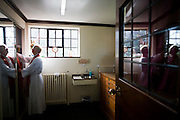 Priest chooses Cassock before morning Mass in Sacristy (Vestry) at St. Lawrence's Catholic church in Feltham, London.
