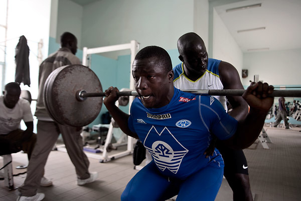 """Papa Sow, Lamb's wrestler of age 28, 96kg and 1.77 mt, lifts 140kg. He is member of Ecurie Fass generation of Parcelles, one of the oldest group of traditional fighters. Dakar, Senegal, on tuesday, April 07 2009.....""""Lamb, the wolof word for fight, is a very popular type of African wrestling in Senegal. This """"lutte traditionelle"""" has been transformed into a national cult, drawing massive following next only to football. Senegalese wrestlers are among the best-known national sports figures. The senegalese fight form allows blows with the hands (frappe), the only of the West African to do so. The lutteurs wrestle in a sandy arena and attempt to win by making their opponent's knees, shoulder, or back touch the sand. Matches are festive and lively occasions, with music, dancing, and praise singing for the athletes; the actual wrestling bouts, however, are often over within a few seconds. Presently, wrestling is arranged by business-promoters who offer prizes for the winners..The sport has produced its own legends, names such as Yékini, Tyson and Bombardier (stage names) are celebrities in Senegal. In particular Mohammed Ndao, aka Tyson,  the 34-year-old leader of the Boul Falé generation of Pikine, a Dakar suburb, did not only revolutionise the sport, by carving his own group identity, and upsetting the old guard, but he is also credited with insisting on commensurate remuneration for the wrestlers. A """"combat"""" could start from 10 million CFA francs (about 20,000 US dollars) to 65 million CFA francs. (about 130,000 dollars). The phenomenal success is such that stakeholders are already talking about building a separate stadium for the sport in the country."""""""