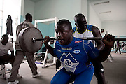 "Papa Sow, Lamb's wrestler of age 28, 96kg and 1.77 mt, lifts 140kg. He is member of Ecurie Fass generation of Parcelles, one of the oldest group of traditional fighters. Dakar, Senegal, on tuesday, April 07 2009.....""Lamb, the wolof word for fight, is a very popular type of African wrestling in Senegal. This ""lutte traditionelle"" has been transformed into a national cult, drawing massive following next only to football. Senegalese wrestlers are among the best-known national sports figures. The senegalese fight form allows blows with the hands (frappe), the only of the West African to do so. The lutteurs wrestle in a sandy arena and attempt to win by making their opponent's knees, shoulder, or back touch the sand. Matches are festive and lively occasions, with music, dancing, and praise singing for the athletes; the actual wrestling bouts, however, are often over within a few seconds. Presently, wrestling is arranged by business-promoters who offer prizes for the winners..The sport has produced its own legends, names such as Yékini, Tyson and Bombardier (stage names) are celebrities in Senegal. In particular Mohammed Ndao, aka Tyson,  the 34-year-old leader of the Boul Falé generation of Pikine, a Dakar suburb, did not only revolutionise the sport, by carving his own group identity, and upsetting the old guard, but he is also credited with insisting on commensurate remuneration for the wrestlers. A ""combat"" could start from 10 million CFA francs (about 20,000 US dollars) to 65 million CFA francs. (about 130,000 dollars). The phenomenal success is such that stakeholders are already talking about building a separate stadium for the sport in the country."""