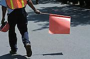 man directing traffic with orange flag