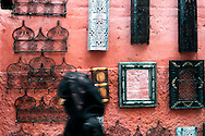 Morocco, Marrakesh. Woman wearing a veil and  passing the street in the pink medina of Marrakesh.