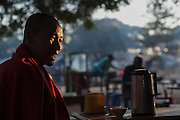 Monk at tea shop having morning tea with sunrise light on face and smiling