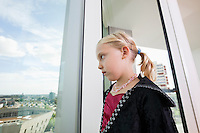 Pensive girl in vampire costume looking out through window at home