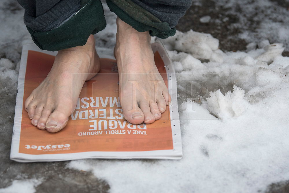 © Licensed to London News Pictures. 03/03/2018. London, UK. A members of the Serpentine Swimming Club keeps his feet warm by standing on newspaper before braving freezing overnight temperatures as they enjoy an early morning dip at sunrise in the Serpentine in Hyde Park, London. Large parts of the UK are recovering from a week of sub zero temperatures and heavy snowfall, following two severe cold fronts. Photo credit: Ben Cawthra/LNP