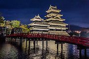 """Lit at night, Matsumoto Castle reflects in the moat by its red bridge. The castle was built from 1592-1614 in Matsumoto, Nagano Prefecture, Japan. Matsumoto Castle is a """"hirajiro"""" - a castle built on plains rather than on a hill or mountain, in Matsumoto. Matsumotojo's main castle keep and its smaller, second donjon were built from 1592 to 1614, well-fortified as peace was not yet fully achieved at the time. In 1635, when military threats had ceased, a third, barely defended turret and another for moon viewing were added to the castle. Interesting features of the castle include steep wooden stairs, openings to drop stones onto invaders, openings for archers, as well as an observation deck at the top, sixth floor of the main keep with views over the Matsumoto city."""