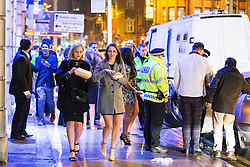 © Licensed to London News Pictures . 01/01/2015 . Manchester , UK . Two women eat takeaways as police attend to an incident . Revellers usher in the New Year on a night out in Manchester City Centre .  Photo credit : Joel Goodman/LNP