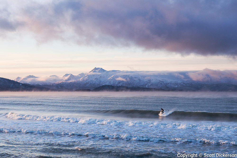 A surfer rides a wave in Kachemak Bay on a cold winter morning at sunrise. The water temperature is in the mid 30s F but warm compared with the air which causes a steam to rise from the ocean.
