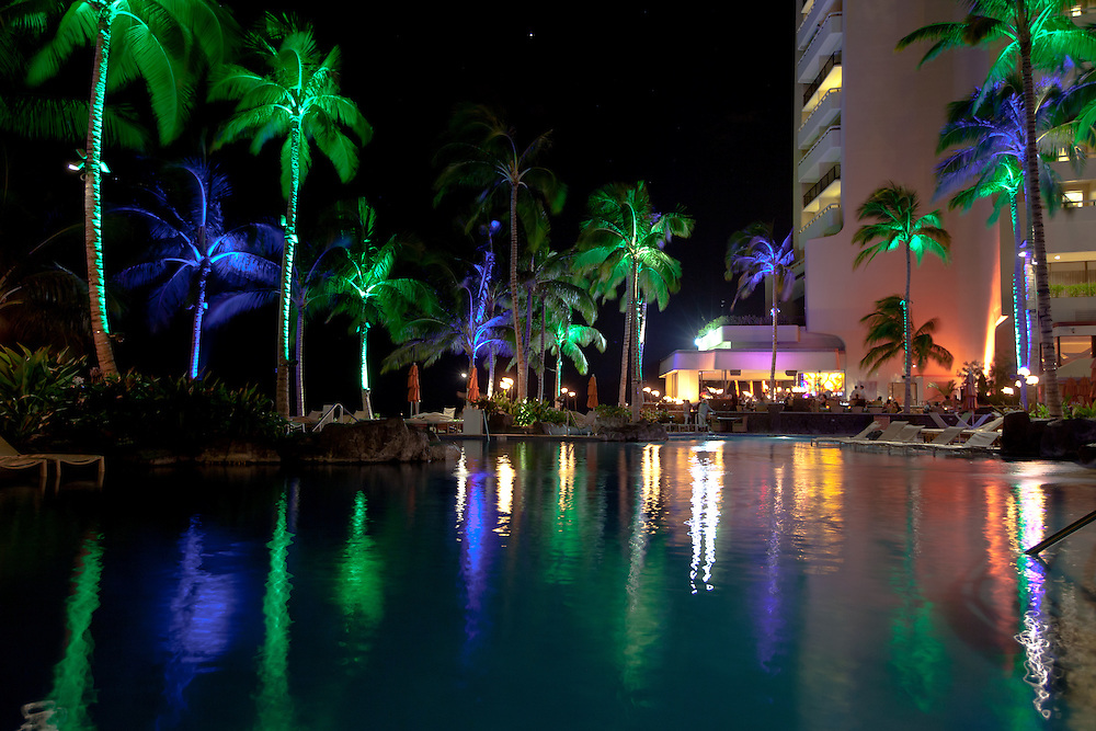 Colorfully lit palm trees reflect in the pool by the beach bar at the Sheraton Resort in Waikiki Beach, Hawaii