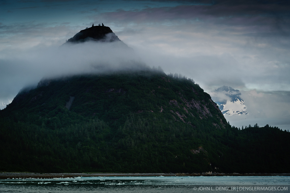 """The Nunatak"" rises out of low clouds near Nunatak Cove in Glacier Bay National Park and Preserve in southeast Alaska. The Nunatak is a 1,205 foot glaciated knob located on the east side of the Muir Inlet."