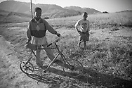 A young boy and his companion pictured with their home-made bicycle on a road through the Drakensberg mountains, north of Mbabane, Swaziland. The Kingdom of Swaziland (population 1.1m), a small, landlocked country in southern Africa was bordered by South Africa on three sides and Mozambique to the east, with Mbabane as its administrative capital. At the start of the 21st century, the country had the highest incidence per head of population of HIV/Aids in the world and and high levels of poverty mainly in rural areas where 75 per cent of the population lived.