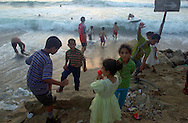 A young Palestinian girl dressed up for a Wedding party eats a candy apple looking on to Palestinians enjoying the Mediterranean beach off the coast of Gaza City Saturday July 28, 2001. Despite the 11 months of violence Israelis and Palestinians take a break to enjoy the Mediterranean beaches and the Dead Sea, where under growing tensions and in the case of Gaza under closure people try to  make the best of their summer and carry on a normal life.