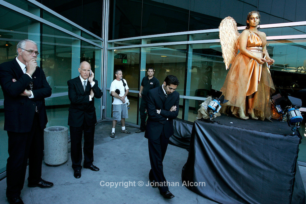 9-15-201-2010  Los Angeles, CA   California Democratic gubernatorial Governor Jerry Brownspeaks on his mobile phone with members of his staff standing by during a break at a campaign appearance at a Mexican Independence Day celebration at Staples Center in Los Angeles. A live model dressed as an angel stands at the event sponsored by the Mexican consulate in Los Angeles.