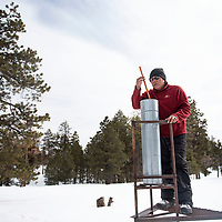 Wilson Wauneka, an engineering technician with the Navajo Nation Department of Water checks the precipitation in a rain can at the Whiskey Creek SNOTEL site in the Chuska mountains, Tuesday, Jan. 29.