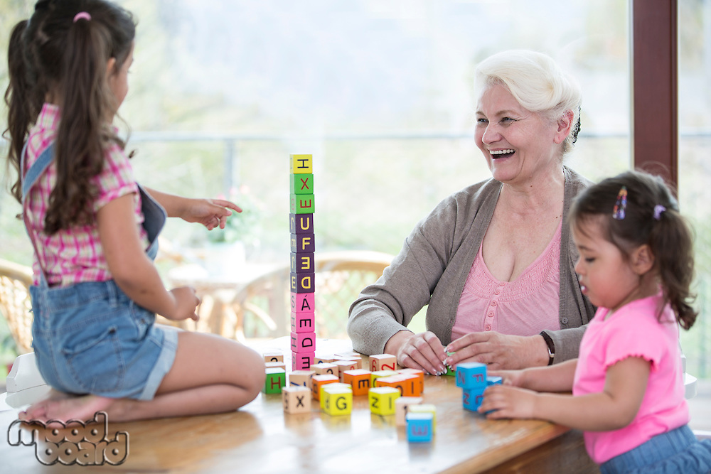 Happy grandmother and granddaughters playing with alphabet blocks at table