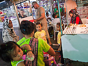 06 JULY 2011 - BANGKOK, THAILAND: A Thai souvenir vendor with a baby on her back sells novelties to an Arab family in the Soi Arab neighborhood of Bangkok. Soi Arab is an alleyway in Bangkok. What started as an alley has now grown into a neighborhood that encompasses several blocks of restaurants, hotels and money exchanges that cater to Middle Eastern visitors to Thailand. The official name of the street is Sukhumvit Soi 3/1, located in North Nana between Sukhumvit Soi 3 and Sukhumvit Soi 5, not far from the Nana Plaza night-life area and the Grace Hotel popular among Arabs.   PHOTO BY JACK KURTZ