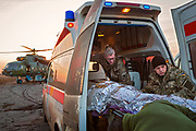 With other members of ASAP, Julia Paevska is evacuating a volunteer named Sergey to a helicopter in Bakhmut, a town in eastern Ukraine's conflict zone, carrying him to a better hospital in the city of Dnipropetrovsk. He was wounded when a sniper bullet hit the van he was driving in Zaitseve, close to the frontline, as he was bringing humanitarian aid to civilians alongside another volunteer, who was also injured.