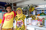 Nur Khayati, 24, and her brother who helps with her fruit smoothie business.<br /> <br /> Nur was working in a restaurant when she downloaded the Usaha Wanita app. She wasn't planning to go into business then but the stories and advice about the need for women to be independent inspired her so much that she decided to invest her savings in setting up a juice stall.<br /> <br /> Her fruit is purchased daily and the juices are freshly prepared in front of the customer. <br /> <br /> Her business is just four months old but is already thriving. She has been able to give her parents 6 million rupiah, which they are investing in land to increase the size of their fruit farm. <br /> <br /> She is also opening a new booth in another part of town in two weeks time.