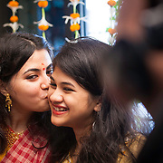 Haldi ceremony or hould kota before bengali wedding. Beautiful bride and a sister candid movement.`