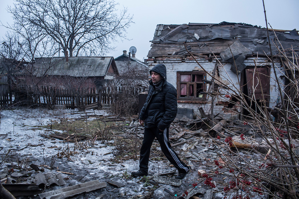 DONETSK, UKRAINE - JANUARY 28, 2015: A man shows a neighbor's house which was damaged by shelling earlier in the day in the Petrovskyi district of Donetsk, Ukraine. The area, in the city's southwest, is close to heavy front-line fighting in Marinka. CREDIT: Brendan Hoffman for The New York Times
