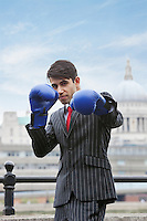 Portrait of an Indian businessman wearing blue boxing gloves with St. Paul's Cathedral in the background