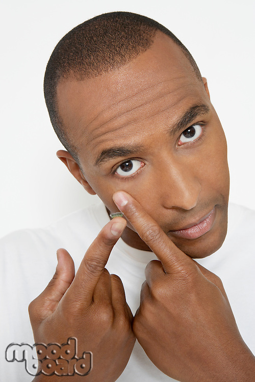 Man applying contact lens, portrait
