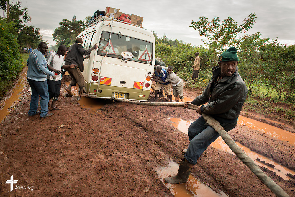 Men attempt to free a bus carrying the Medical Mercy Team from deep mud on a road Tuesday, June 10, 2014, in rural Kakmega County, Kenya. The team walked to the clinic and the bus was freed several hours later. LCMS Communications/Erik M. Lunsford