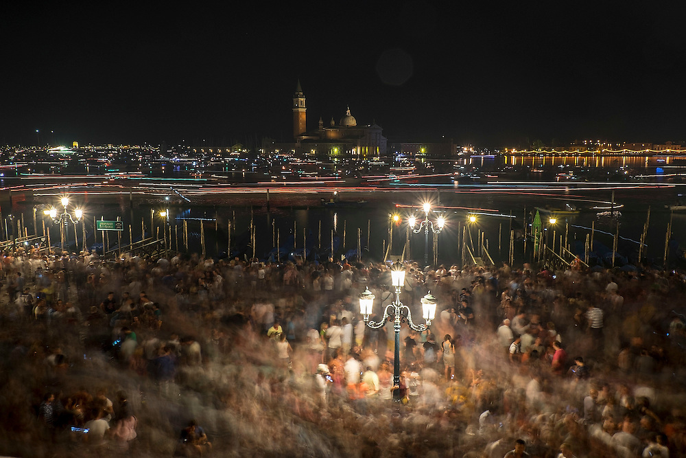 VENICE, ITALY - JULY 19:  Party goers, gondolas and boats are captured on a long exposure leaving St. Mark's Basin after the fireworks display for the Redentore Celebrations on July 19, 2014 in Venice, Italy. Redentore , which is in remembrance of the end of the 1577 plague, is one of Venice's most loved celebrations. Highlights of the celebration include the pontoon bridge extending across the Giudecca Canal, gatherings on boats in the St. Mark's Basin and a spectacular fireworks display.  (Photo by Marco Secchi/Getty Images)