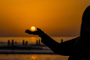 Sunset over the sea. The sun in the palm of her hand