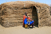 Maasai Woman and baby sit in front of her mud and straw hut. Maasai is an ethnic group of semi-nomadic people. Photographed in Tanzania