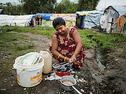 05 AUGUST 2015 - KATHMANDU, NEPAL: A woman does her dishes in a large Internal Displaced Person (IDP) Camp in the center of Kathmandu. The camp is next to one the most expensive international hotels in Kathmandu. More than 7,100 people displaced by the Nepal earthquake in April live in 1,800 tents spread across the space of three football fields. There is no electricity in the camp. International NGOs provide water and dug latrines on the edge of the camp but the domestic waste water, from people doing laundry or dishes, runs between the tents. Most of the ground in the camp is muddy from the running water and frequent rain. Most of the camp's residents come from the mountains in northern Nepal, 8 - 12 hours from Kathmandu. The residents don't get rations or food assistance so every day many of them walk the streets of Kathmandu looking for day work.    PHOTO BY JACK KURTZ