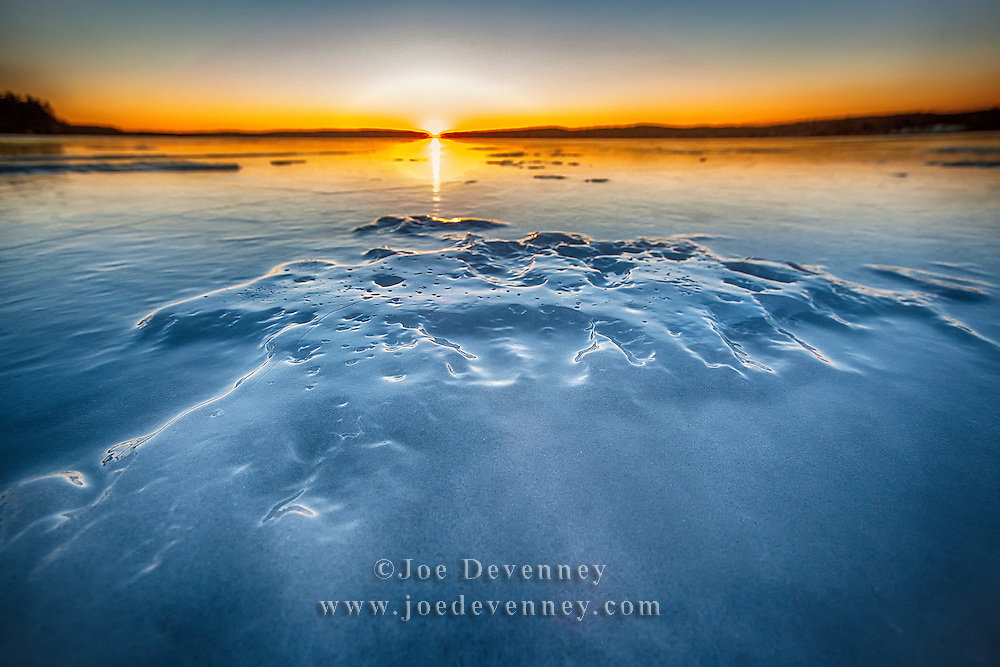 Sunset on a frozen lake. Winter in northern Maine