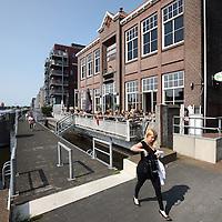 Nederland, Zaandam , 5 juli 2013.<br /> Wandeling door de binnenstad van Zaandam.<br /> Starten bij De Werf aan de Oostzijde. Daarvandaan kun je lopen op een soort boulevard tussen de flats en het water. De eerste stop is De Fabriek, filmhuis en eetcafé met terras aan de Zaan met uitzicht op de sluis. Daarna de sluis zelf.<br /> Dan langs het winkelgebied richting de Koekfabriek: Het oude Verkade pand dat is verbouwd en waar nu de bieb en sportschool en restaurant etc. in zitten.<br /> (Dat is aan de overkant van het startpunt) en misschien nog de Zwaardemaker meepakken aan de Oostzijde. Dat is een oud pakhuis die Rochdale enige jaren geleden heeft verbouwt tot appartementen met een stukje Nieuwbouw.<br /> Ook doen: het Russische buurtje vlakbij de Zaan. Dit jaar staat Rusland in de schijnwerpers en Zaandam heeft een speciale band met Rusland, vanwege het Czaar Peterhuisje en de Russische buurt. <br /> Op de foto: De Fabriek aan de Oostzijde<br /> Foto:Jean-Pierre Jans