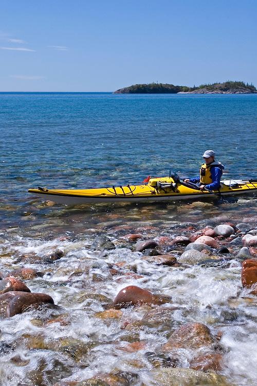 A small stream spills over cobblestones as a sea kayaker paddles Gargantua Harbor in Lake Superior Provincial Park near Wawa Ontario Canada.