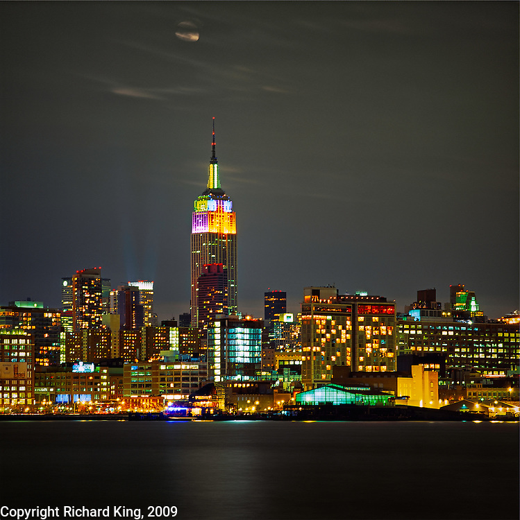 Empire State Building, Manhattan showing unusually varied colored lighting with the full moon peering out from the clouds
