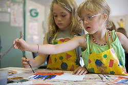 Two nursery school girls painting pictures in art lesson,