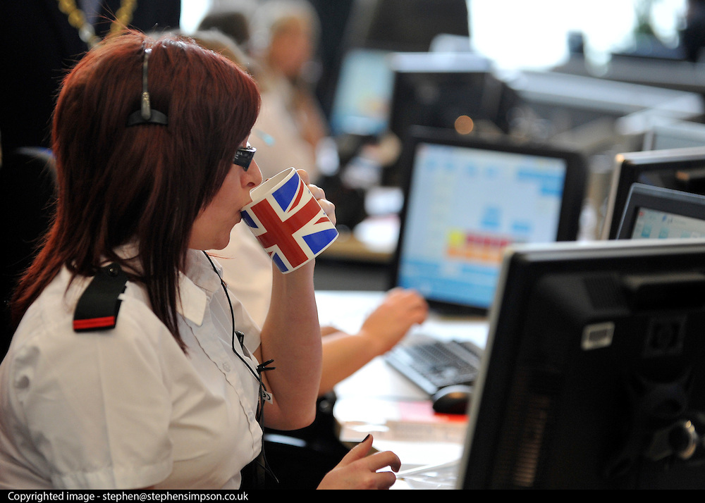 © Licensed to London News Pictures. 01/02/2012, London, UK. A member of Emergency room staff drinks from a mug bearing the Union Jack. handle incoming 999 calls from London. Mayor of London Boris Johnson and Fire Minister Bob Neill, MP open the centre. The opening of a state of the art new fire control centre ahead of the London 2012 Olympic and Paralympic Games. The London Operations Centre (LOC) brings together in a secure, bomb proof building London Fire Brigade's control centre, London's emergency planning teams and by April the National Co-ordination Centre.Photo credit : Stephen Simpson/LNP