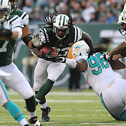 Running back Chris Ivory, New York Jets, is tackled by Paul Soliai, Miami Dolphins, during the New York Jets Vs Miami Dolphins  NFL American Football game at MetLife Stadium, East Rutherford, NJ, USA. 1st December 2013. Photo Tim Clayton