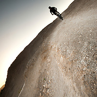a mountain biker makes his way across the stark desert landscape of gypsum underneath a clear sky.  the stark and beautiful landscape of the white mesa bike trails, near the small town of san ysidro, new mexico, usa, provides an inimitable mountain bike experience to the adventuresome soul.