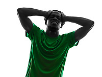 one african man soccer player green jersey despair loosing in silhouette on white background