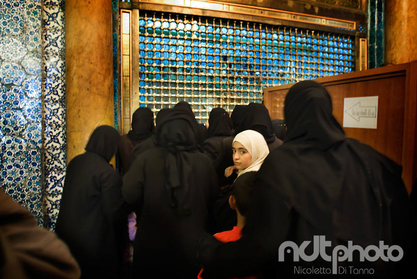 A white-veiled girl, part of a group of black-veiled women worshipping Zechariah's shrine in the Omayyad Mosque in Aleppo, turns her head to look back