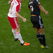 Nov 8, 2015; Harrison, NJ, USA; New York Red Bulls midfielder Dax McCarty (11) and D.C. United forward Alvaro Saboru (9)\ go up for a head ball during the second half of the MLS Playoffs at Red Bull Arena. Mandatory Credit: William Hauser-USA TODAY Sports