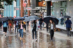 © Licensed to London News Pictures. 10/08/2018. London, UK. Shoppers shelter beneath umbrellas on Oxford Street in London as rain falls in the capital. Photo credit: Rob Pinney/LNP