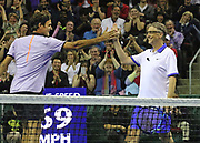 """Swiss player Roger Federer, left, congratulates Bill Gates after they win a point in the set in which they also won 6-4 over pro John Isner and Mike McCready (lead guitarist with Pearl Jam). """"The Match for Africa 4 Seattle,"""" held at KeyArena, was the fourth charity tennis event for the Roger Federer Foundation. (Alan Berner/The Seattle Times)"""