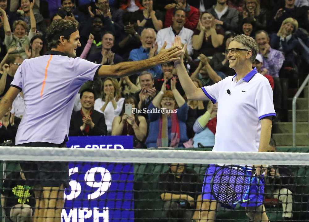 "Swiss player Roger Federer, left, congratulates Bill Gates after they win a point in the set in which they also won 6-4 over pro John Isner and Mike McCready (lead guitarist with Pearl Jam). ""The Match for Africa 4 Seattle,"" held at KeyArena, was the fourth charity tennis event for the Roger Federer Foundation. (Alan Berner/The Seattle Times)"